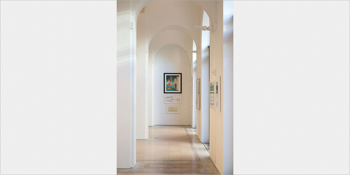 Gallery arcade with Solavanti Kera indirect sconces uplighting the vaulted ceiling.