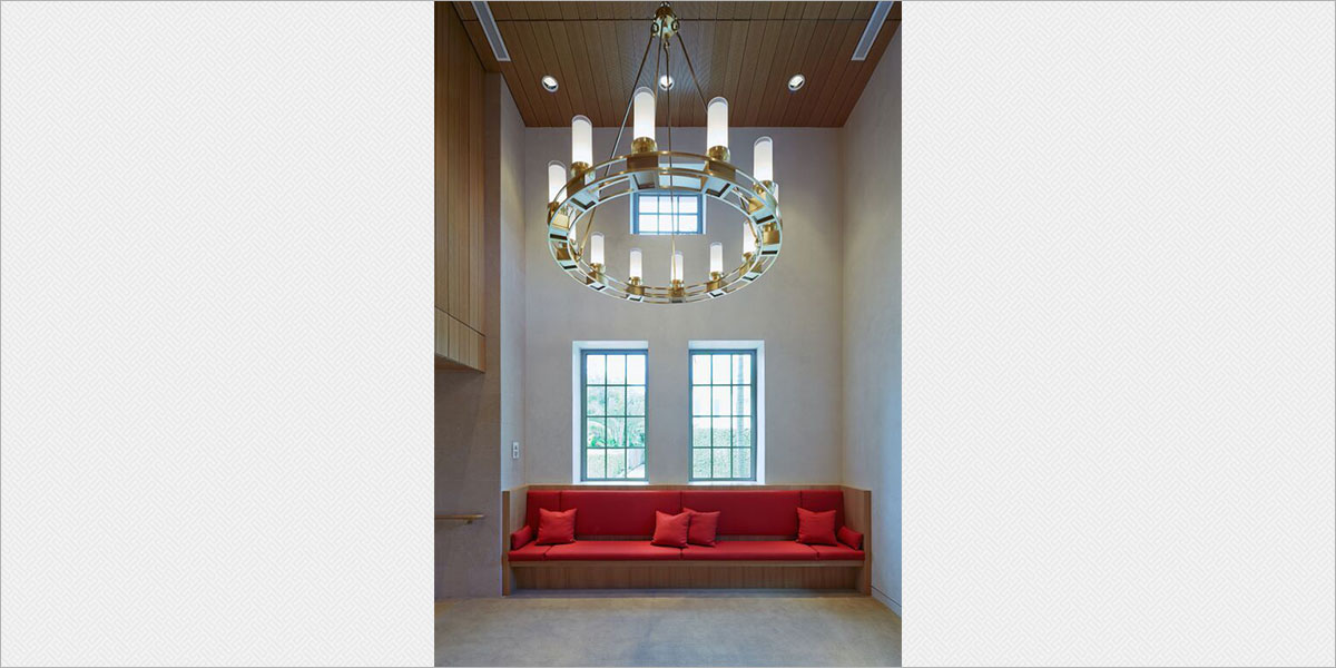 Custom 60-in diameter brass chandeliers by Crenshaw Lighting in the theatre lobby.